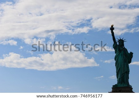 Statue of Liberty in silhouette against blue sky with clouds