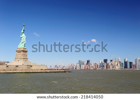 Statue of Liberty on Liberty Island and New York City Manhattan downtown skyline with skyscrapers and blue sky - stock photo