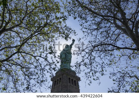 Statue of Liberty seen between tree branches on Liberty Island - stock photo