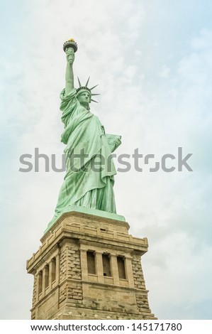 Statue of Liberty shot on an overcast day. The varied coatings of patina are clearly visible. - stock photo