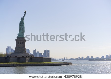 Statue of Liberty with Brooklyn Bridge in background - stock photo