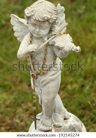 statue of little angel playing violin  - stock photo