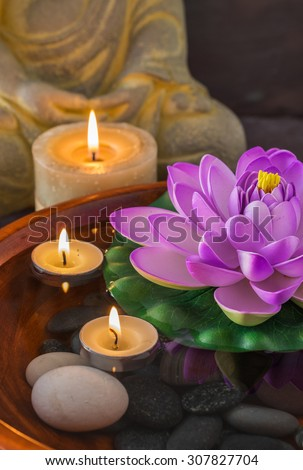 Statue of meditating Buddha and a Lotus flower floating with candles - stock photo