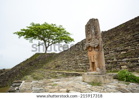 statue of ruler Jaguar Bird Peccary in Tonina Chiapas Mexico with solitary tree in the background on a rainy day  - stock photo