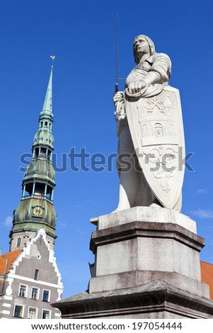 Statue of Saint Roland with St. Peter's church in the background in riga, Latvia.