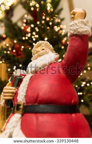 Statue of Santa before a christmas tree. Twinkle lights in the background.