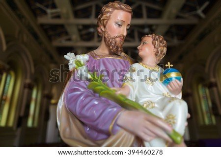 Statue of st Joseph and a baby inside a catholic church with selective focus. - stock photo