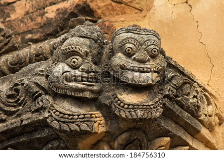 statue of two faces(full face) on the corner of ancient temple in Bagan(Pagan), Myanmar(Burma)  - stock photo