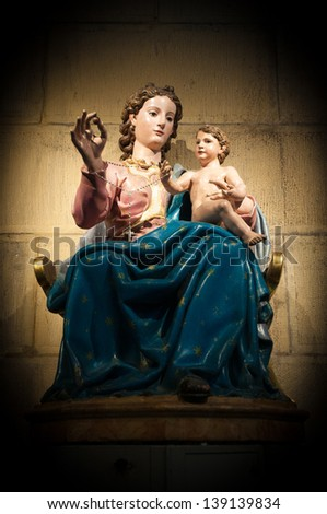 Statue of Virgin Mary sitting with Jesus on her knee, they hold together chain with cross. Artwork in catholic church in spotlight. Decoration and interior of cathedral. Religion and faith. - stock photo