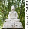Statue of White buddha against bamboo background - stock photo