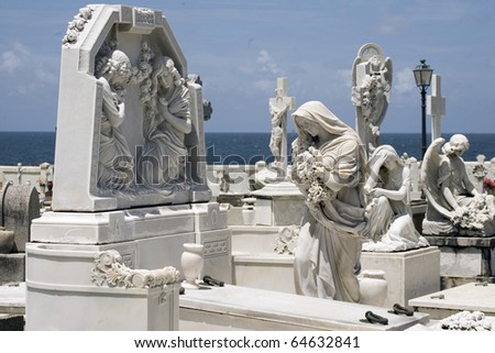 Statue of woman in mourning with angels nearby.  Located inside Santa Maria Magdalena de Pazzis cemetery in Old San Juan Puerto Rico.