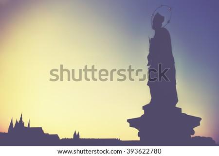 Statue on Charles Bridge (Karluv most, 1357), a famous bridge that crosses Vltava River in Prague, Czech Republic, low contrast and blur concept, sunset - stock photo