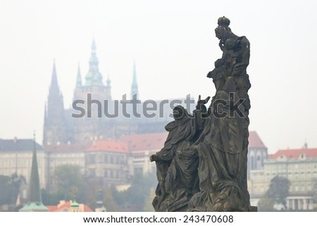 Statue on the Charles bridge and distant Prague castle in cloudy autumn day, Prague, Czech Republic - stock photo