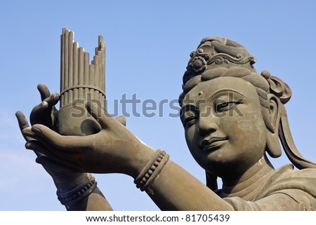 Statue providing offering at a Buddhist temple in Lantau Island, Hong Kong - stock photo
