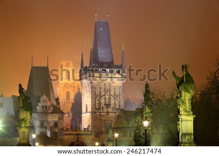 Statues illuminated on the Charles bridge and distant Gothic tower surrounded by fogg during night, Prague, Czech Republic - stock photo