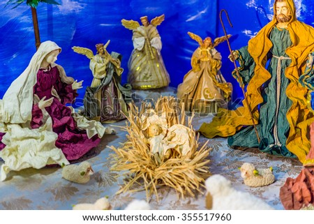 Statues in a Christmas Nativity scene, the Blessed Virgin Mary and Saint Joseph watch over the Holy Child Jesus - stock photo