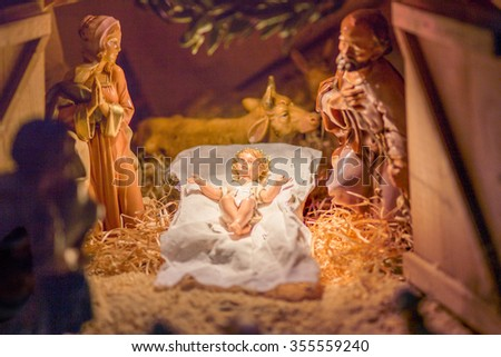 Statues in a Christmas Nativity scene, the Blessed Virgin Mary and Saint Joseph watch over the Holy Child Jesus in a manger in the straw while the ox and the donkey are warming air - stock photo