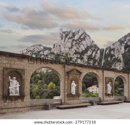 Statues in the Court Yard and Mountains of Montserrat at Sunset - stock photo