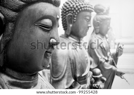 Statues of Ancient gods buddha and Avalokitasvara stand three abreast in temple. - stock photo