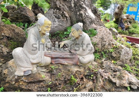 Statues of Confucius philosopher are playing chess - stock photo