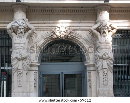 Statues of two strong men seeming to hold the entire building. - stock photo