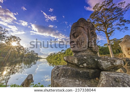 Statues on the bridge at the entrance of Angkor Thom - stock photo