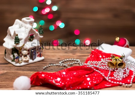 statuette New Year / Christmas house on a wooden table and Christmas balls and bells on a background color bokeh of Christmas lights