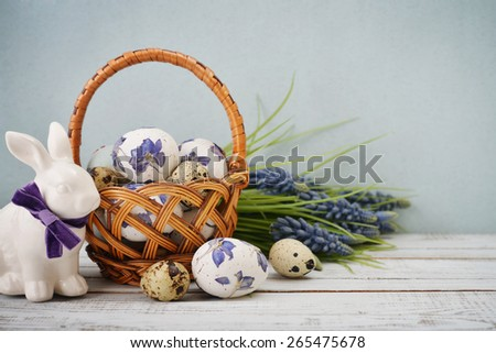 Statuette of rabbit with easter eggs in basket  and hyacinth bouquet on wooden background