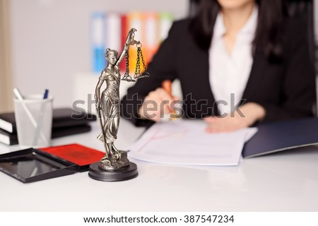 Statuette of Themis - the goddess of justice on lawyer's desk. Lawyer is stamping the document. Law office concept.  - stock photo