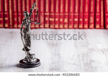 Statuette of Themis the symbol of law on old wooden floor with legal codes. Law concept