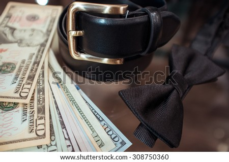 Status accessories for the businessman (a belt and a tie) in shop of fashionable men's wear and dollars - stock photo