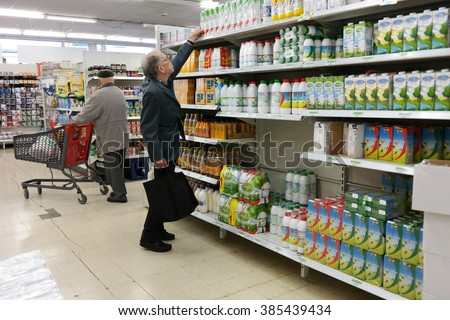 STAVELOT, BELGIUM - JULY 27,  2015: Customer chooses UHT milk on aisle with sterilizes diary in a SPAR supermarket. Spar is a Dutch multinational retail chain operates in 35 countries worldwide. - stock photo