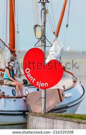 STAVOREN, THE NETHERLANDS - SEPTEMBER 3, 2014: Classic wooden sailing boat leaving the Stavoren harbor with an exit sign with the text 'Goodbye' in the province of Friesland, The Netherlands - stock photo