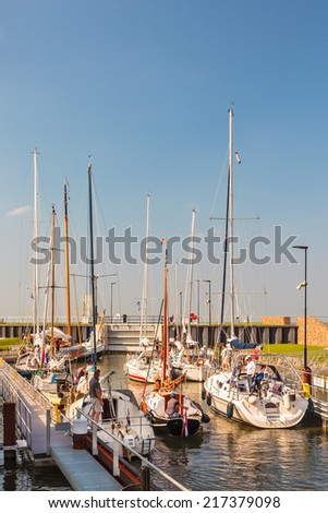 STAVOREN, THE NETHERLANDS - SEPTEMBER 4, 2014: Sailing boats waiting in a sluice before entering the IJselmeer in Stavoren in the province of Friesland, The Netherlands - stock photo