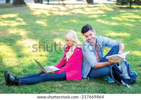 Stay after school. Student girl and boy student hold a laptop and looking at the camera while sitting on the grass near the campus of the University at the break. Couple showing thumbs up. - stock photo