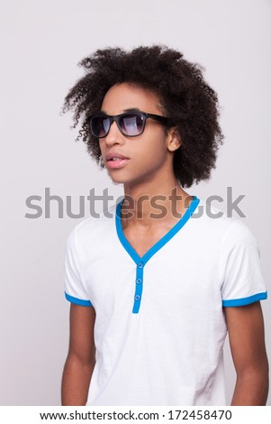 Stay cool! Teenage African boy in sunglasses standing isolated on grey background - stock photo