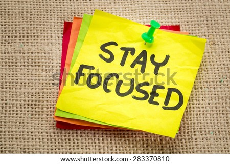 stay focused reminder on a sticky note - motivation concept - stock photo