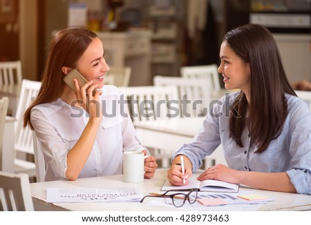 Stay positive. Cheerful delighted beautiful friends sitting at the table and communicating while resting