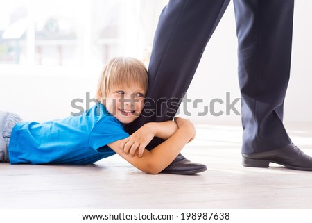 Stay with me! Playful little boy embracing his father leg and smiling while lying on the floor  - stock photo