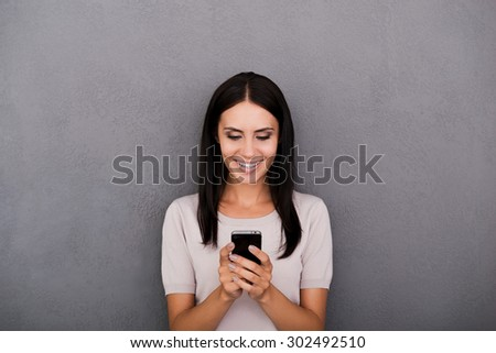 Staying connected. Cheerful young woman holding smart phone and smiling while standing against grey background - stock photo
