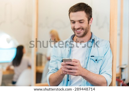 Staying connected. Happy young man looking at his mobile phone and smiling while his colleagues working in the background - stock photo