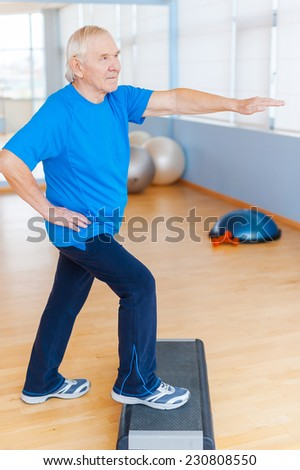 Staying healthy and active. Full Length of confident senior man doing step aerobics in health club - stock photo
