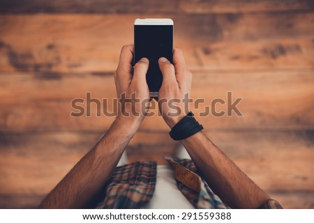 Staying in touch. Top view of man holding smart phone while standing on the wooden floor  - stock photo