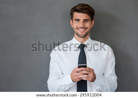 Staying in touch with my colleagues. Handsome young man in shirt and tie holing mobile phone and smiling while standing against grey background - stock photo