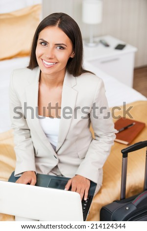 Staying in touch with my colleagues. Top view of beautiful young businesswoman in suit working on laptop and smiling while sitting on the bed in hotel room  - stock photo