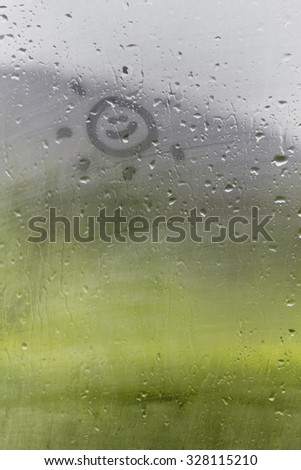 Staying positive - Smiley sun drawn on the foggy glass window on - stock photo