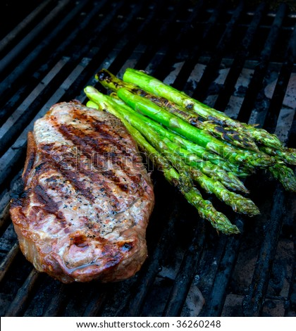 Steak and asparagus on hot barbecue grill - stock photo