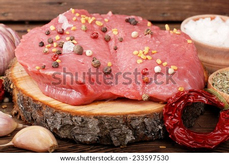 Steak and spices on a wooden surface - stock photo