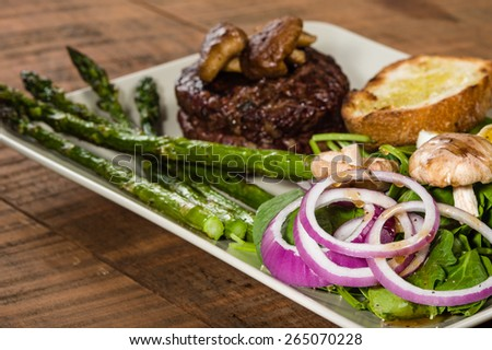 Steak and spinach salad with onion rings and mushrooms - stock photo