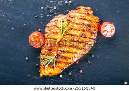 Steak chicken breast olive oil cherry tomatoes pepper and rosemary herbs. Steak chicken breast on granit board. - stock photo